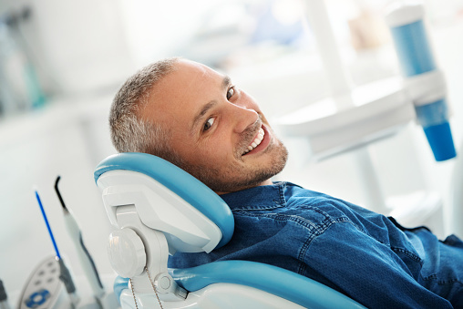 A smiling man in a dental office chair